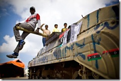 Libya 1st April 2011 -- Children play on a tank used by Benghazi based Anti Gadaffi freedom fighters 10km outside the recaptured town of Brega and on route to the ever moving frontline bomb rebel 'Shabaab' freedom fighters despite being bombed by Nato aircraft. Gadaffi's forces regaining ground close to Ajdabiya  for the sixth time in two weeks. This after the coalition forces handed over the defensive action to Nato who has ceased bombing targets that were seen as harmful to civilians in Libya. On 8 April, loyalist forces attempted to recapture the city. Taking advantage of a disorganised rebel retreat following the Third Battle of Brega, loyalist troops entered the city and had taken control of most of it by 9 April. However, rebel forces soon regrouped and had pushed pro-Gaddafi forces out of the city by 11 April, with heavy support from NATO airstrikes. The front line then stagnated outside of the city, 40 km down the road to Brega. Loyalist shells continued to intermittently strik